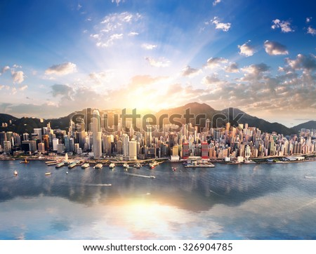 Hong Kong skyline. Hongkong hdr aerial cityscape with sunset sun. Amazing panorama of buildings and sky reflecting in harbour Royalty-Free Stock Photo #326904785