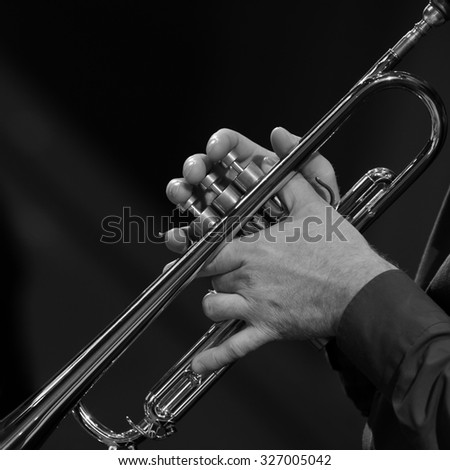 Hands of a man playing a trumpet in black and white #327005042