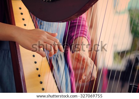 Closeup of a woman playing the harp with soft retro filter effect lighting or instagram filter Royalty-Free Stock Photo #327069755