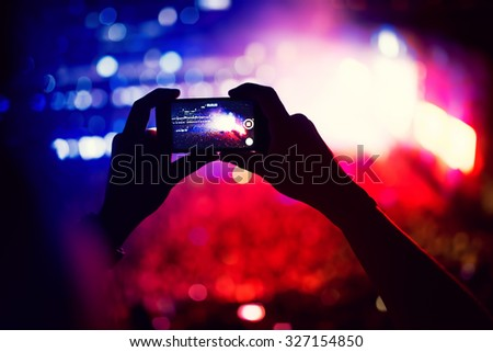 silhouette of a young man using camera phone for recording a live concert #327154850