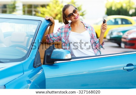 Young pretty woman in sunglasses standing near convertible with keys in hand - concept of buying a used car or a rental car Royalty-Free Stock Photo #327168020