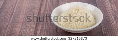 Grated cheese in white bowl over wooden background #327215873