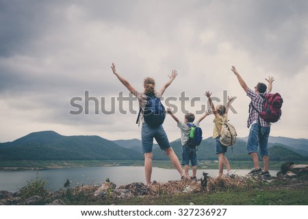 Happy family standing near the lake at the day time.  Concept of friendly family. #327236927