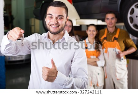 portrait two young troubleshooters showing fixed car to satisfied client #327242111