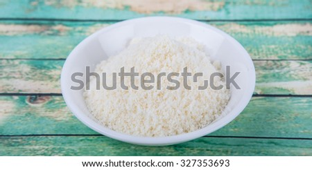 Grated cheese in white bowl over wooden background #327353693