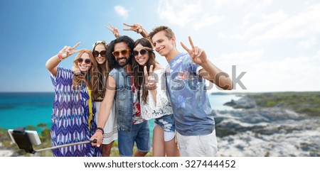 summer holidays, vacation, travel, technology and people concept - smiling young hippie friends taking picture by smartphone on selfie stick and showing peace gesture over beach background #327444452
