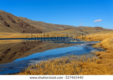 Bright picturesque mountain autumn landscape with a lake, mountains reflecting in the lake, with snow on the banks and a cloud against the blue sky on a sunny day #327465440