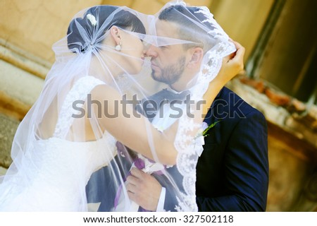 bride and groom kissing under the veil #327502118
