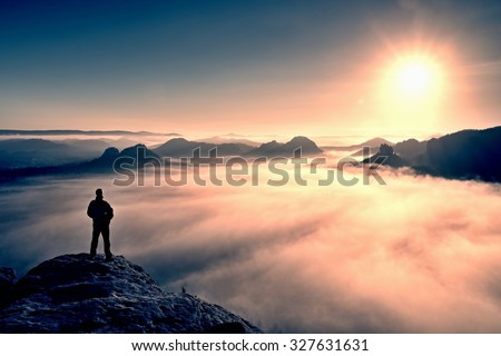 Man stands on the peak of sandstone rock in national park Saxony Switzerland and watching to Sun. Beautiful moment the miracle of nature. Misty valley. Man hike.Person silhouette stand.Foggy mountains #327631631