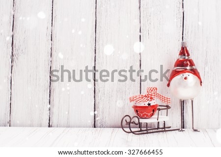 Xmas or new year composition with sledge, little bell and funny bird on white wooden background. Xmas card. Space for text. Selective focus Royalty-Free Stock Photo #327666455