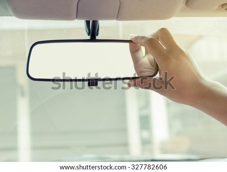 Hand adjusting rear view mirror. Royalty-Free Stock Photo #327782606