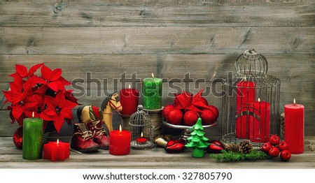 Christmas decoration red candles, flower poinsettia, stars and baubles. Retro style dark toned picture
