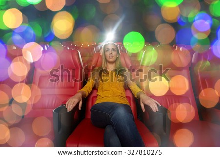 cinema, entertainment and people concept - young woman watching movie alone in empty theater auditorium #327810275