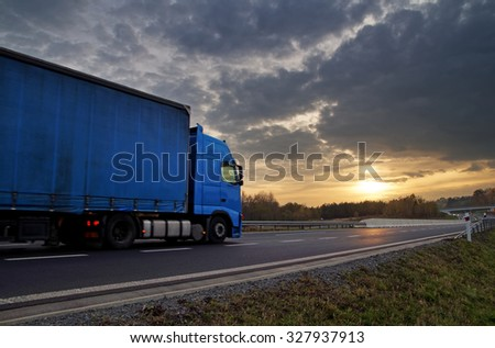 Blue truck on highway at sunset in the countryside. Dark clouds in the sky. #327937913