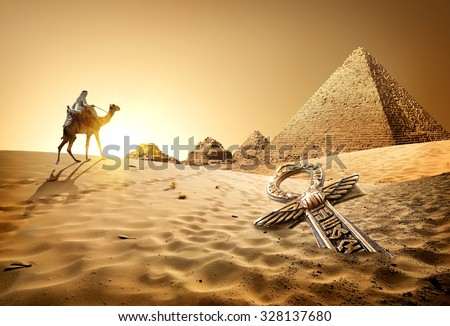 Bedouin on camel near pyramids and ankh in desert #328137680