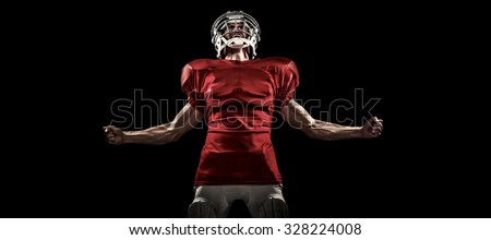 Aggressive American football player in red jersey screaming against black #328224008