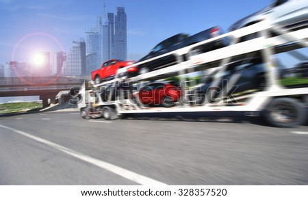 The trailer transports cars on highway with big city background  #328357520