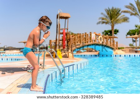 Young boy preparing to dive into a swimming pool at a vacation resort standing on the tiled surround in his swimsuit and goggles, profile view #328389485