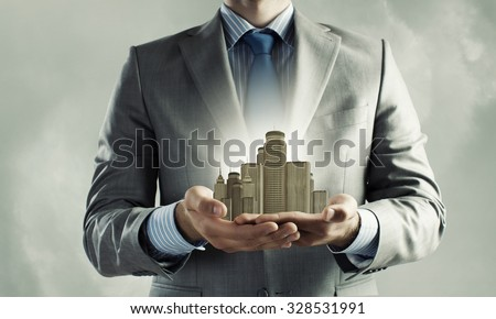 Close up of businessman holding modern office center model in hands #328531991