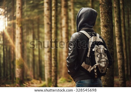 Young hooded man hiking in the woods, freedom and nature concept #328545698