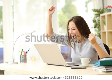 Euphoric winner watching a laptop on a desk winning at home Royalty-Free Stock Photo #328558622