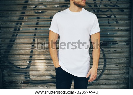 Young man wearing white blank t-shirt and blue jeans, standing on the street Royalty-Free Stock Photo #328594940