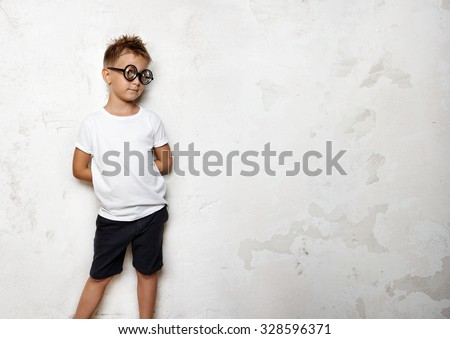 Little boy holds his hands behind back and looks funny #328596371