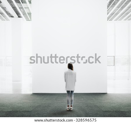 Young woman walking through a gallery and looking at the canvas