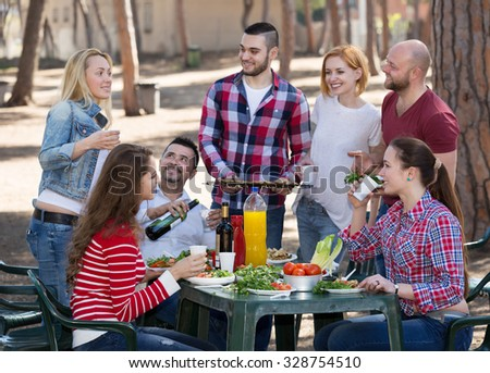 Cheerful happy friends posing and taking pictures together at the barbecue  #328754510