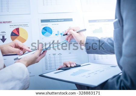 Business people discussing the charts and graphs showing the results of their successful teamwork Royalty-Free Stock Photo #328883171