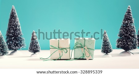 Little green handmade gift boxes in a snow covered miniature evergreen forest