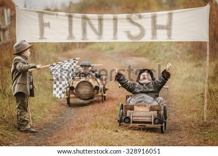 Finish of competition between the two little boys racers on homemade wooden car. Retouch for retro Royalty-Free Stock Photo #328916051