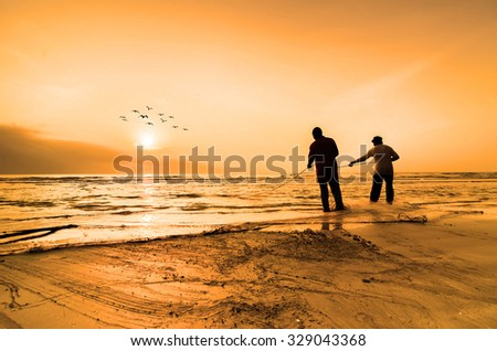 KUANTAN, MALAYSIA - JULY 20, 2014 - Fishermen do their work near Beserah beach, Kuantan, Malaysia at July 20, 2014. Fishermen are the main occupation for villagers at Kuantan village, Pahang #329043368