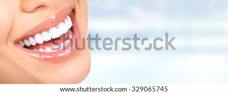 Laughing woman mouth with great teeth over blue background.