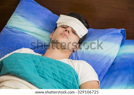 Young handsome sick or unwell man in bed with a flu or fever  #329106725
