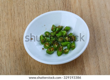 Green chili pepper on the wood background #329193386