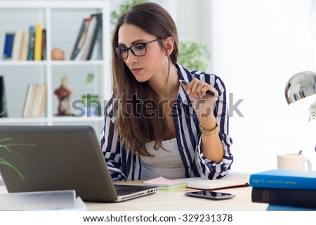 Portrait of beautiful young woman working in the office. Royalty-Free Stock Photo #329231378