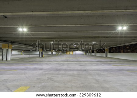 Empty parking garage at night with city panorama #329309612