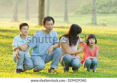 Family lying outdoors being playful and smiling #329429360