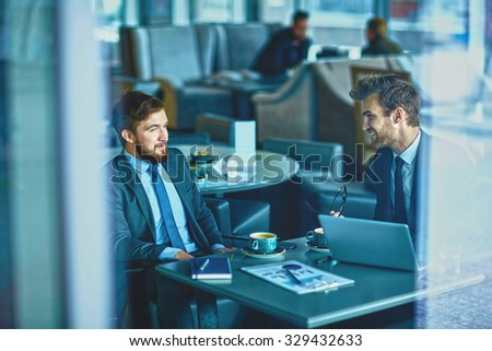 Two male employees consulting in cafe #329432633