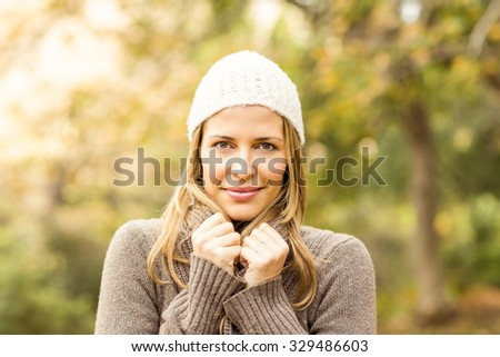 Portrait of smiling woman holding her scarf on an autumns day #329486603