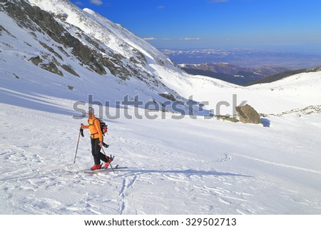 Isolated ski mountaineer climbs moderate slope on snow covered mountain  #329502713