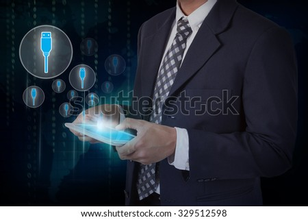 Businessman hand touch screen flash drive icons on a tablet. #329512598