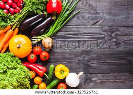 Background of wooden planks black color with fresh vegetables. #329526761