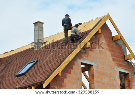 Roofing Construction and Building New Brick House with Modular Chimney, Skylights, Attic, Dormers and Eaves Exterior. Roofers Install, Repair Asphalt Shingles or Bitumen Tiles on the Rooftop Outdoor. #329588159