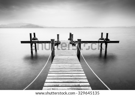 Wooden pier on the lake. Fog. Long exposure. Black and White. #329645135