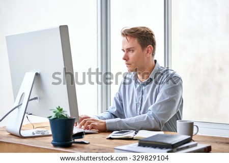Handsome young businessman typing on his keyboard while sitting at his desk working  #329829104