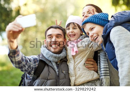 travel, tourism, hike, technology and people concept - happy family with backpacks taking selfie by smartphone outdoors