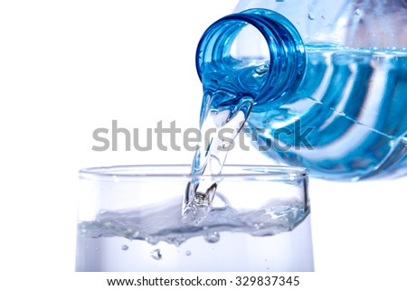 Water poured from a plastic bottle into a glass, isolated on white #329837345