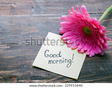 "Gerbera flower and piece of paper with text ""good morning"" on the wooden table close-up"